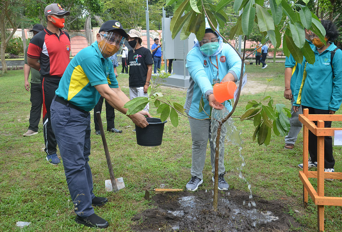 Bupati Kobar didampingi Kepala DLH sedang menyiram tanaman Bintaro (Cerbera Mangas)